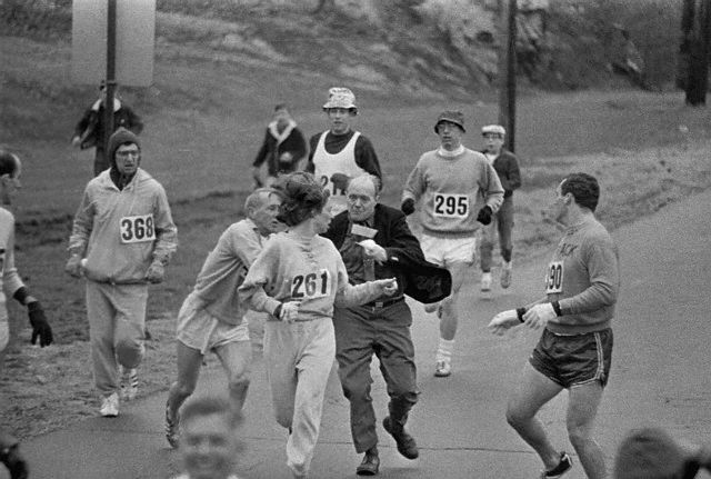 19 Apr 1967, Hopkinton, Massachusetts, USA --- The rule that no women shall run in the Boston Athletic Association (BAA) Marathon is being put to a very real test in this photo. Trainer Jack Semple (in street clothes) enters the field of runners to try to pull Kathy Switzer (261) out of the race. Male runners move in to form protective curtain around the female track hopeful, until the protesting trainer is finally wedged out of the race, and the lady is allowed to finish the marathon. --- Image by © Bettmann/CORBIS