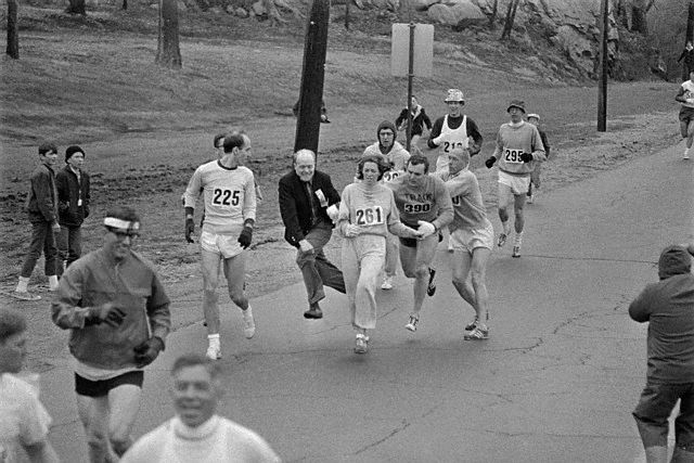 19 Apr 1967, Hopkinton, Massachusetts, USA --- In the Boston Marathon, one of two women running in the normally all-male-race, Kathy Switzer, (261) of Syracuse, New York, is being hassled by BAA Marathon Director Bill Cloney, as he attempted to stop her from competing. The dark-haired girl did not show up for the physical examination required of all starters, (had she appeared at the starting line, she would never have been allowed to compete). she remained in the race, but was never seen near the finish line. --- Image by © Bettmann/CORBIS