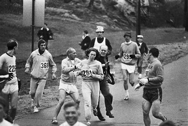 19 Apr 1967, Hopkinton, Massachusetts, USA --- Trainer Jock Semple -- in street clothes -- enters the field of runners (left) to try to pull Kathy Switzer (261) out of the race. Male runners move in to form a protective curtain around female track hopeful until the protesting trainer is finally wedged out of the race --- Image by © Bettmann/CORBIS