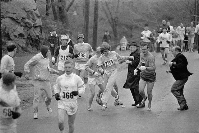 19 Apr 1967, Hopkinton, Massachusetts, USA --- In the Boston Marathon, one of two women running in the normally all-male race, K. Switzer, (261) of Syracuse, New York, gets past Marathon Director Bill Cloney, (in dark suit) here, who attempted to stop her from running. The dark-haired girl did not show up for physical examination required of all starters, (had she appeared at the starting line, she would never have been allowed to compete). She remained in the race, but was never seen near the finish line. --- Image by © Bettmann/CORBIS