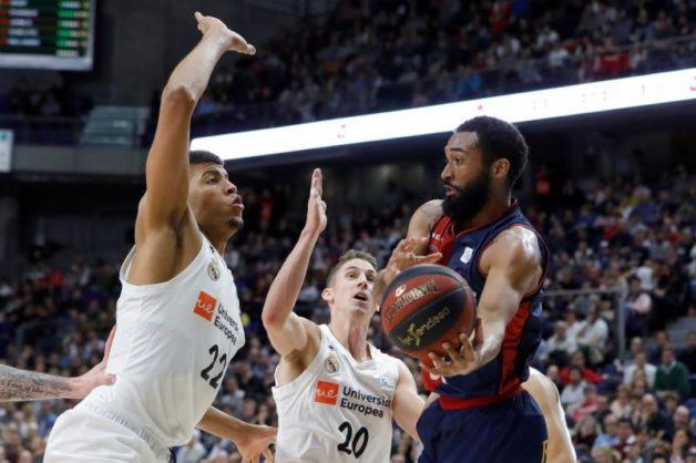 El estadounidense Darrun Hilliard (d), del Baskonia, entra a canasta ante Edy Tavares (i) y Jaycee Carroll (c), ambos del Real Madrid, durante el partido de la jornada 20ª de Liga ACB. EFE/Juanjo Martin