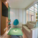 Sala de estar con mesa verde y silla azul